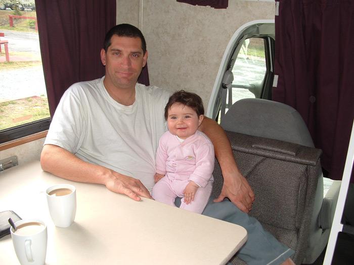 אבא ותינוקת יושבים בתוך קרוואן